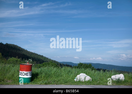 Garbage can on side of road overlooking rolling landscape - Stock Photo