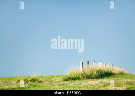 Fence ending in the middle of field - Stock Photo