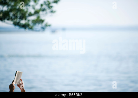 Hands holding book up, tranquil lake in background - Stock Photo