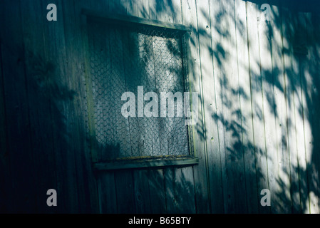 Wooden wall, boarded up window covered with chicken wire - Stock Photo