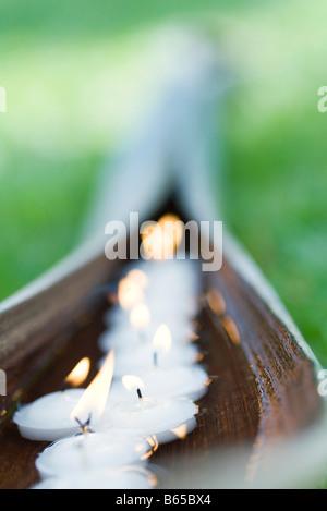 Lit votive candles on palm leaf - Stock Photo