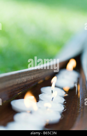Lit votive candles floating in water cupped within palm leaf - Stock Photo
