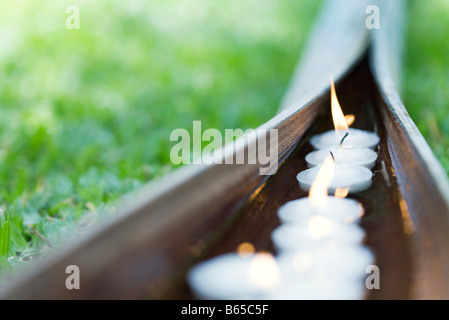 Lit votive candles floating in water in palm leaf - Stock Photo