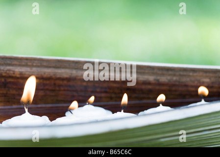 Lit votive candles in natural setting - Stock Photo
