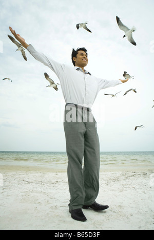 Businessman standing on beach with arms raised, birds flying overhead - Stock Photo