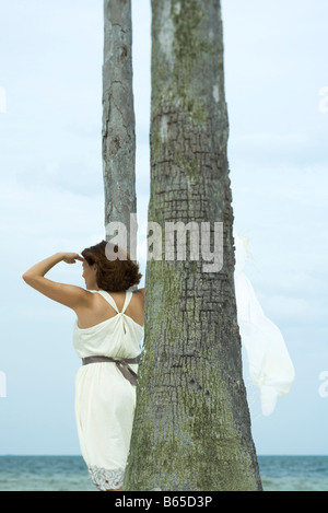 Woman standing amongst palm trees, looking at view of ocean, rear view - Stock Photo