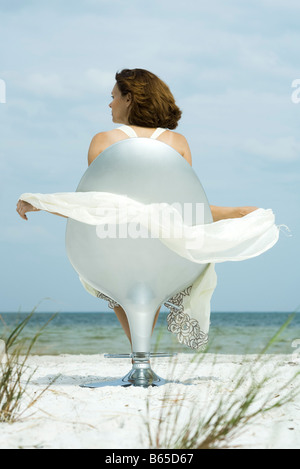 Woman sitting in chair on beach, looking at view, scarf blowing in breeze - Stock Photo