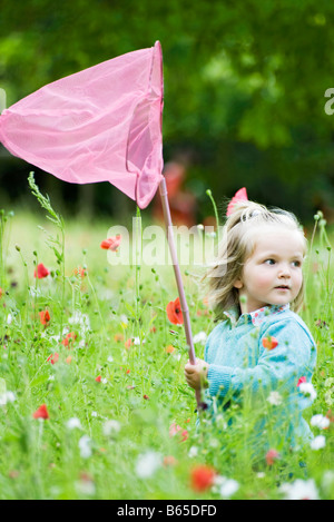 Girl holding up butterfly net, standing in field of flowers - Stock Photo