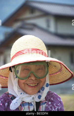 Portrait of an old lady with goggles cutting grass - Stock Photo
