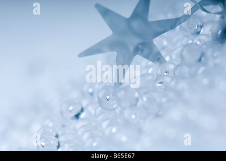 Star ornament and plastic garland, close-up - Stock Photo