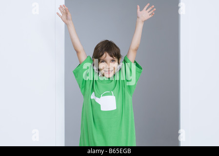Boy wearing oversized tee-shirt with watering can printed on it, arms raised in the air, smiling - Stock Photo