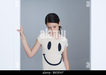 Preteen girl wearing smiley face tee-shirt, frowning, looking down - Stock Photo
