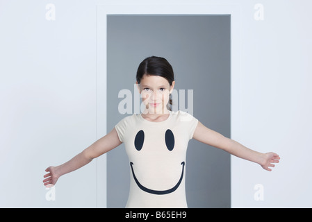 Preteen girl wearing smiley face tee-shirt, arms out, smiling at camera - Stock Photo