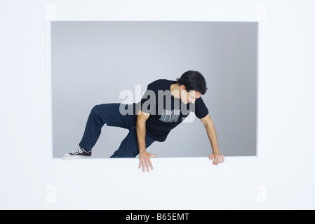 Man climbing over wall, wearing tee-shirt with bar code printed on it - Stock Photo