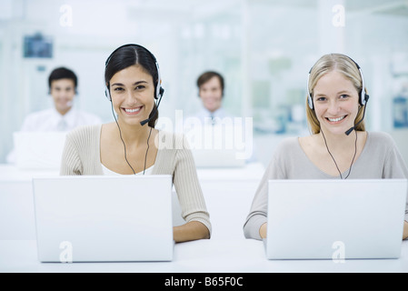 Telemarketers working in call center, smiling - Stock Photo