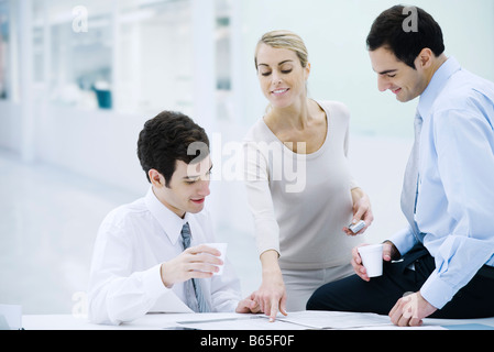 Three professionals taking a coffee break, woman pointing at newspaper - Stock Photo