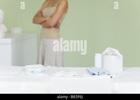 Woman standing in nursery, arms folded, cropped - Stock Photo