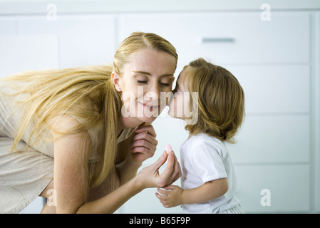 Little girl kissing mother's cheek, woman holding a tiny heart, eyes closed - Stock Photo