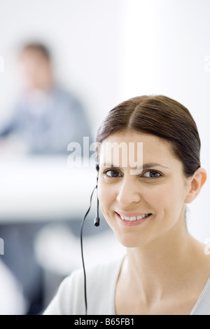 Woman wearing headset, smiling at camera, portrait - Stock Photo