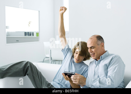 Teen boy showing handheld video game to father, arm raised - Stock Photo