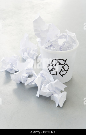 Crumpled paper overflowing recycle bin, close-up - Stock Photo