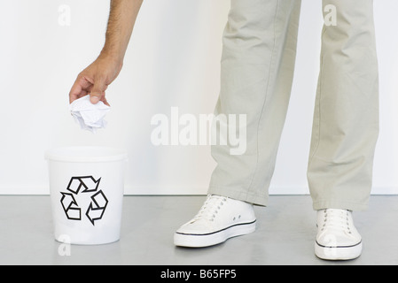 Hand placing crumpled paper into recycle bin, close-up - Stock Photo