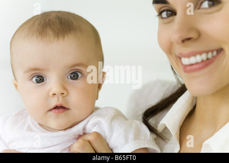 Mother holding baby, smiling at camera - Stock Photo