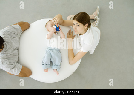 Mother playing with infant lying on ottoman, father sitting with back turned to them, overhead view - Stock Photo