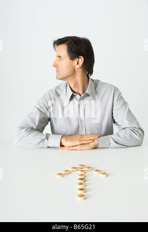 Man sitting at table, Chinese chess pieces in shape of arrow pointing to him, looking away - Stock Photo