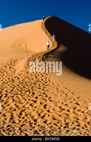 People make the early morning climb of Dune 45 in the Namib Naukluft National Park Sesriem Namibia - Stock Photo