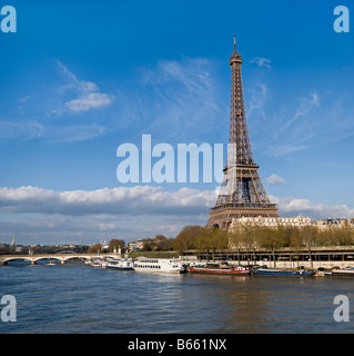 Eiffel Tower with blue skies and boats on the Seine River by Charles W. Lupica - Stock Photo