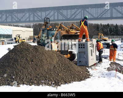 construction workers on a job site in winter - Stock Photo