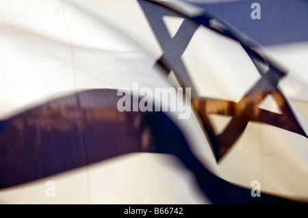 A picture of the Israeli flag blowing in the wind and appears ablaze in the Jerusalem wind - Stock Photo