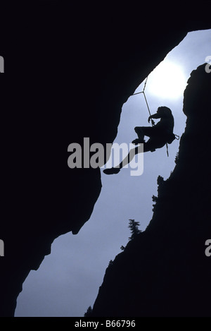 Silhouette of rock climber hanging from cliff face - Stock Photo