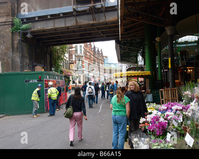People at flower stand at Borough market London UK - Stock Photo