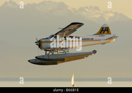 Commuter float plane preparing to land in harbour with Olympic mountains in background. - Stock Photo