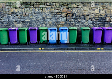 Line of multicoloured recycling bins lined up in front of a stone wall - Stock Photo