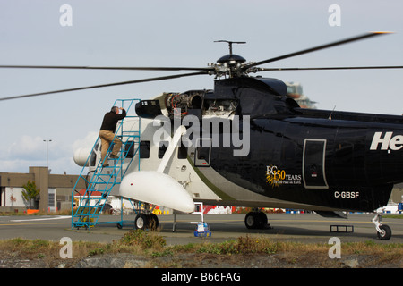Aircraft mechanic working on Sikorski helicopter Victoria British Columbia Canada - Stock Photo