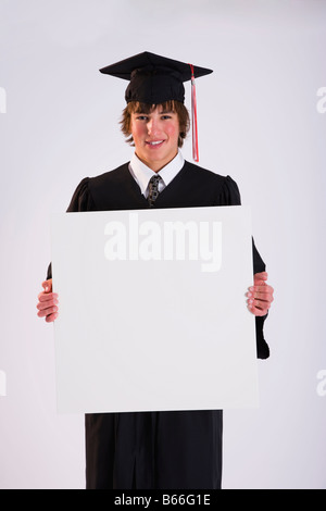 Studio portrait of male graduate in black gown with blank placard - Stock Photo