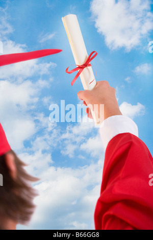 Male graduate in red gown holding up diploma - Stock Photo