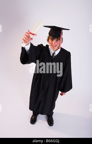 Studio portrait of male graduate in black gown with diploma - Stock Photo