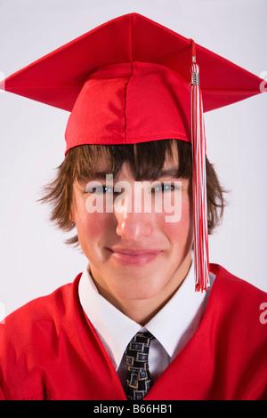 Studio portrait of male graduate in red gown - Stock Photo