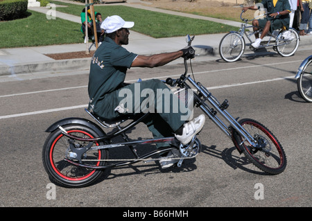 Young African American man proudly showing off his fantastically imaginative bike - Stock Photo