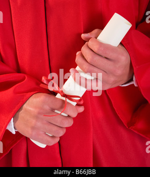 Male graduate in red gown holding diploma, mid section - Stock Photo