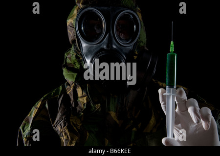 Soldier in respirator and protective suit inspects hypodermic of green liquid - Stock Photo