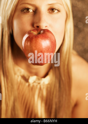 Mid-Adult Woman with Apple in Her Mouth - Stock Photo