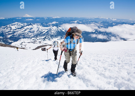 A mid 30's Caucasian woman and her friend hike up the Muir snow field on Mt. Rainier with Mt. Adams, Mt Hood, Mt - Stock Photo