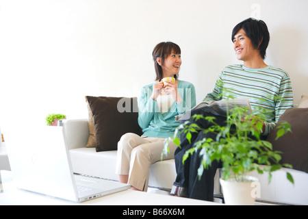 Mid-Adult Couple Talking on Sofa - Stock Photo