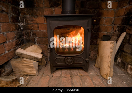 A small energy efficient cast iron wood burning stove with logs, UK - Stock Photo