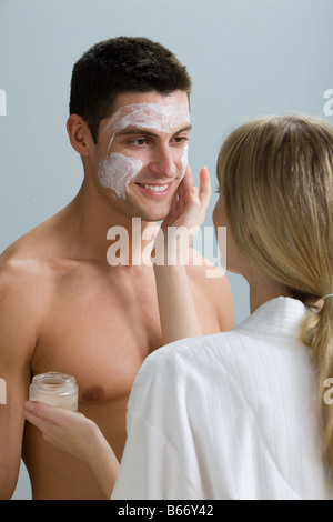 A woman applying face mask to a mans face - Stock Photo